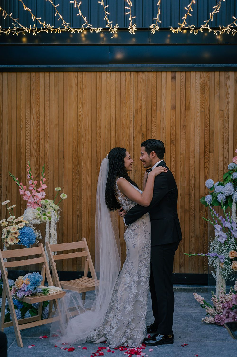 Bride wearing Kazumi Gown in soft grey with hand embellished lace and a low back - hugging at alter