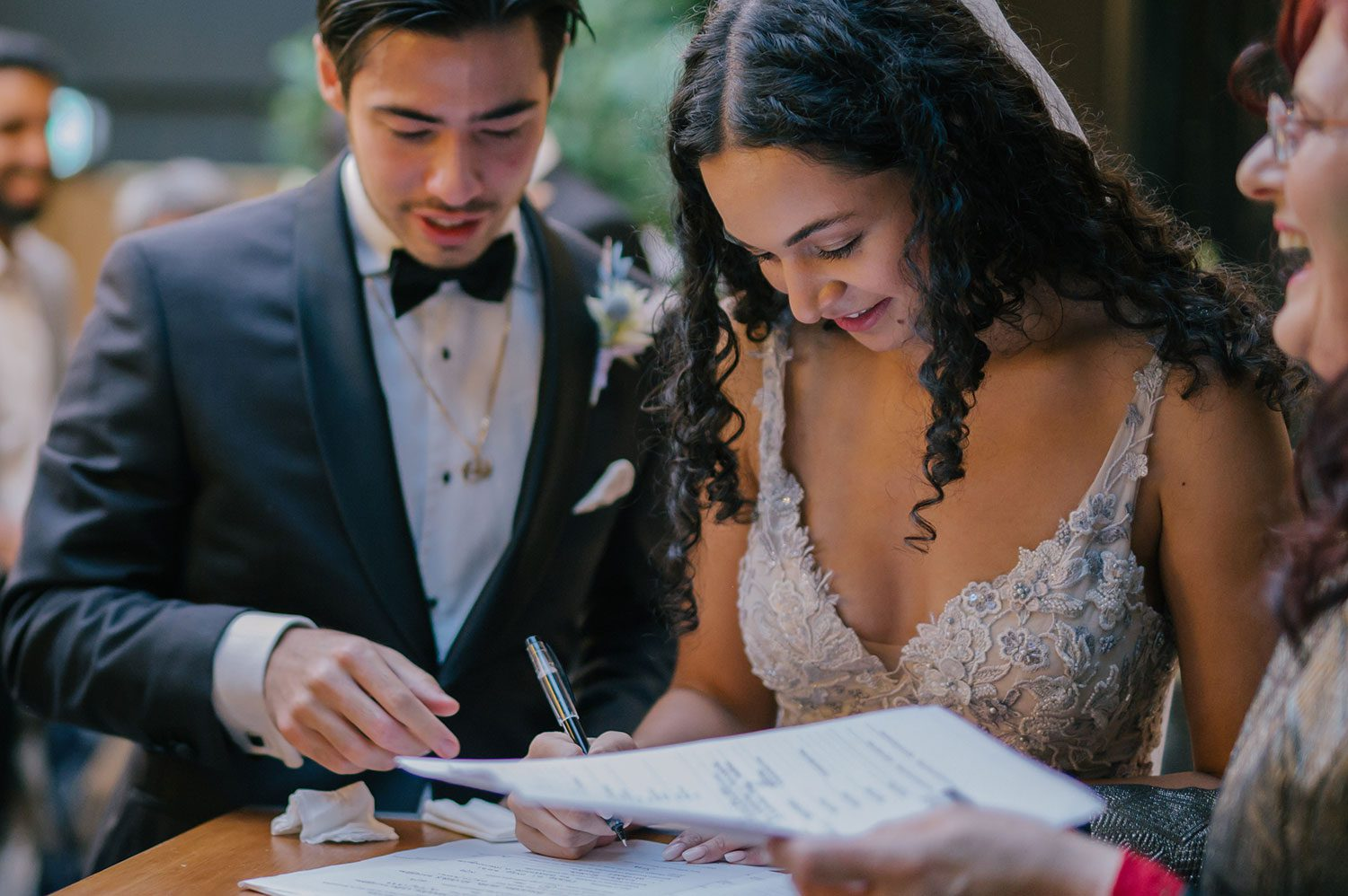 Bride wearing Kazumi Gown in soft grey with hand embellished lace and a low back - siging registrar