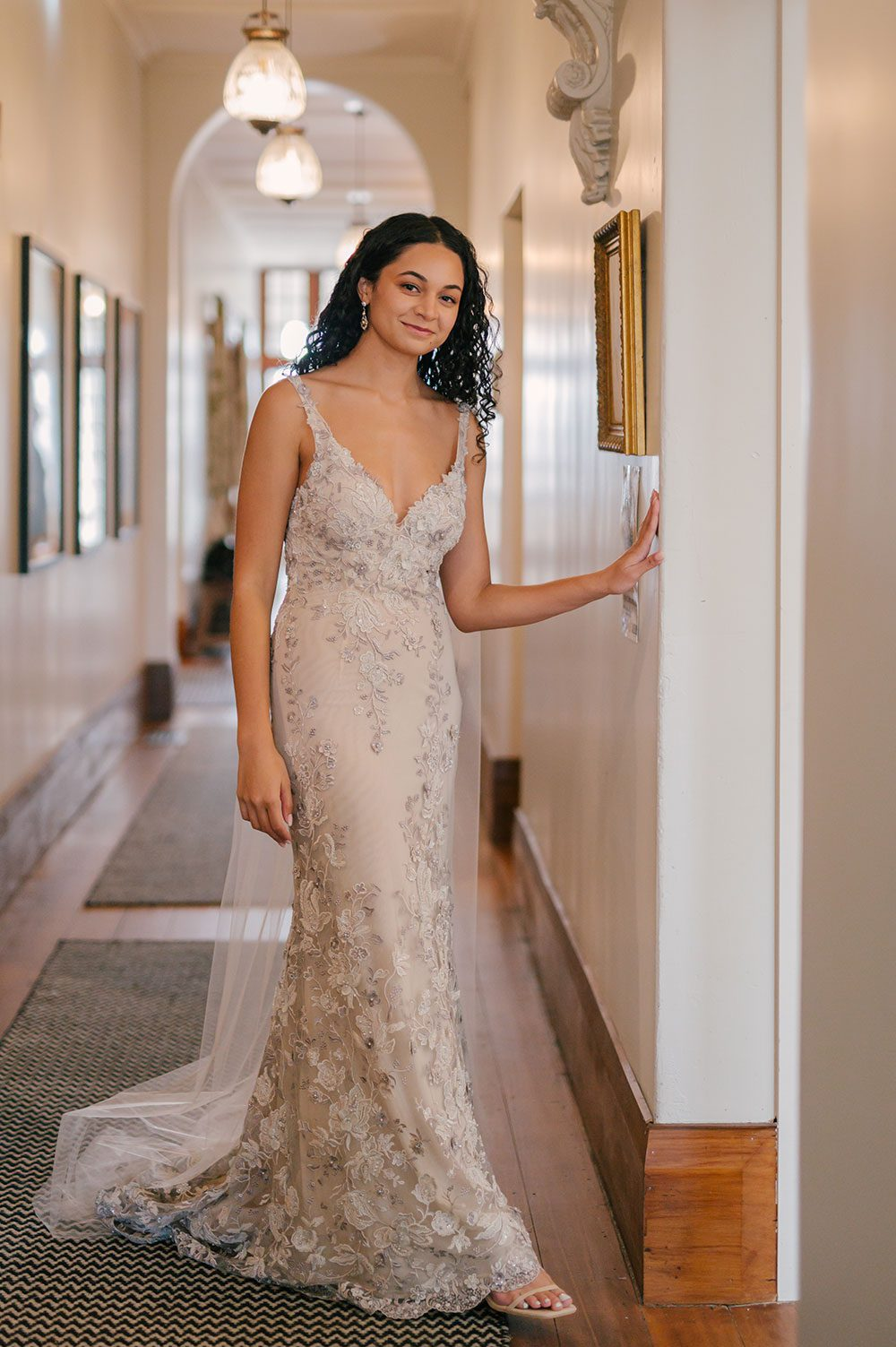 Bride wearing Kazumi Gown in soft grey with hand embellished lace and a low back - in hall